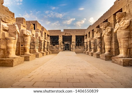 EXPLORING EGYPT - KARNAK TEMPLE - Large sculptures of pharaohs inside beautiful Egyptian landmark with hieroglyphics, and ancient symbols. Famous landmark in the world near Nile River and Luxor, Egypt #1406550839