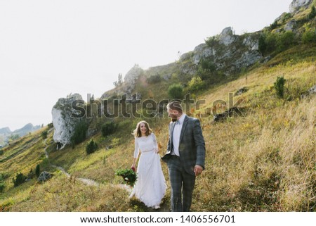 Beautiful bride and groom hug and walk in the mountains at sunset. #1406556701