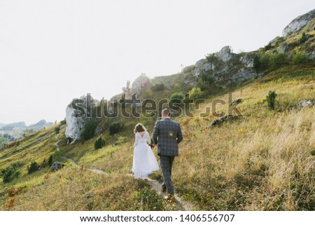 Beautiful bride and groom hug and walk in the mountains at sunset. #1406556707