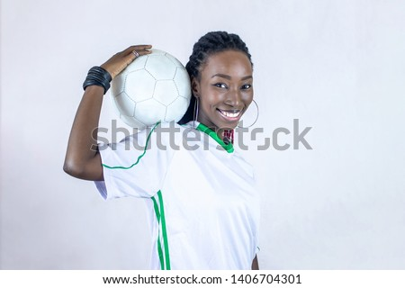 young african soccer player holding his ball on his shoulder smiling #1406704301