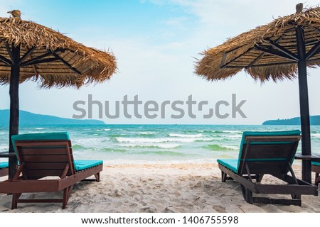 Two chaise lounges and straw umbrella on tropical beach. Coast of island Koh Rong Samloem, Cambodia. free empty copy space for text #1406755598