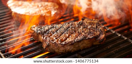 rib-eye steaks cooking on flaming grill panorama #1406775134