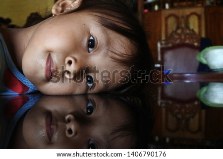 funny little girl photographed on a table with beautiful reflection, Central Java, Indonesia, April 11, 2019 #1406790176