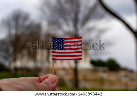 American flag on hand with blurred black ground. #1406893442