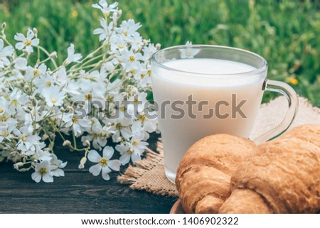 A glass cup of milk stands beside croissants and white small flowers. #1406902322