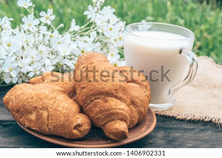 A glass cup of milk stands beside croissants and white small flowers. #1406902331