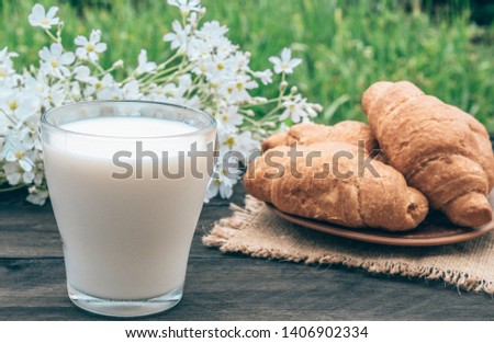 A glass cup of milk stands beside croissants and white small flowers. #1406902334