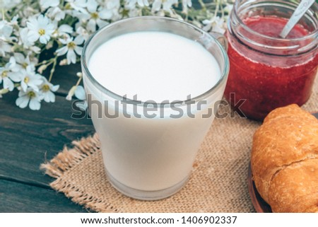 A glass cup of milk stands beside croissants and white small flowers. #1406902337