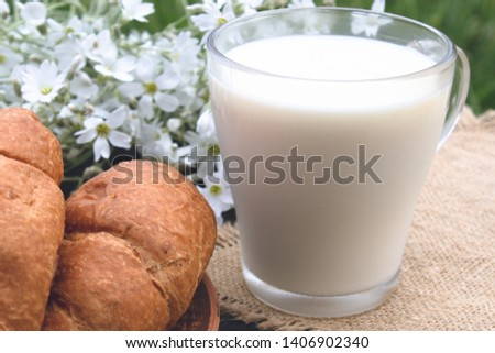 A glass cup of milk stands beside croissants and white small flowers. #1406902340