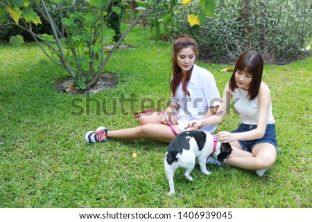 beautiful two young asian woman wearing white shirt who sitting on grass and playing with her cute dog with happy and smiling face in garden with green trees. (friendship concept) #1406939045