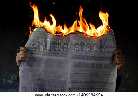 Man protesting fake media news, burning newspaper, dark mode.Burning newspapers in the hand of a man.Against the dark background Royalty-Free Stock Photo #1406984654
