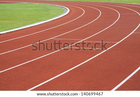 Red running tracks with green grass  and white lines #140699467