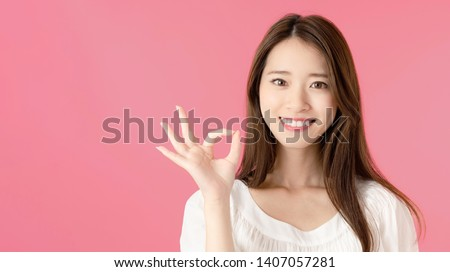 Young asian woman showing a OK hand sign. #1407057281