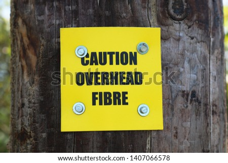 Caution overhead fibre sign. Bright yellow warning sign. #1407066578