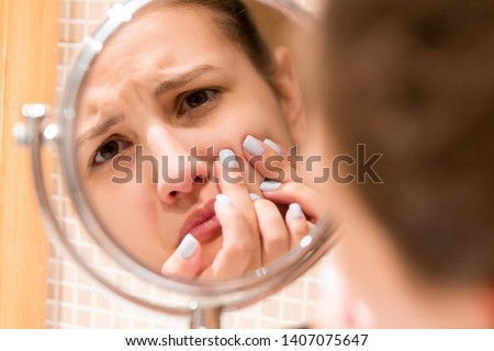 Young girl squeezes pimple on the fer face in front of a bathroom mirror. Beauty skincare and wellness morning concept. #1407075647