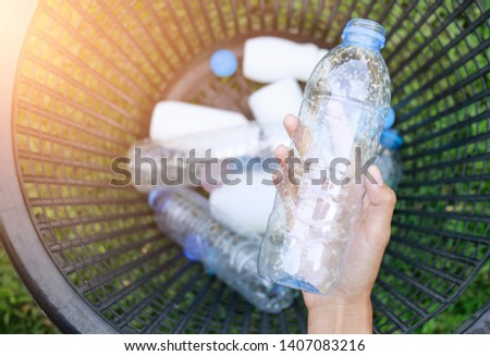 Hand holding reaching to plastic bottle for using in recycle bottles in basket. Plastic free concept for saving environment world  Royalty-Free Stock Photo #1407083216