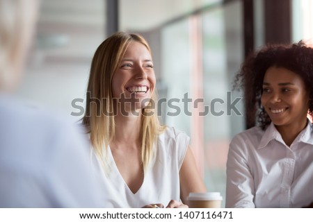Happy young businesswoman coach mentor leader laughing at funny joke at group business meeting, joyful smiling millennial lady having fun with diverse corporate team people engaged in talking at work #1407116471