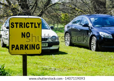 "Sign warning people ""Strictly no parking"", with two cars parked on the grass"