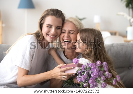Cheerful feminine three diverse generations indoors. Sweet granddaughter mom and laughing grandmother sitting on couch in living room hold gift box and flowers embracing celebrating mother day at home #1407222392