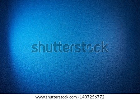 A wide beam of light blue from the side shines on a textured blue background #1407256772