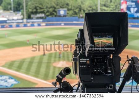 Television broadcast camera shooting at a sunny baseball game