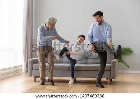 Happy three generations of men have fun dancing feel overjoyed in living room, smiling millennial father, preschooler son and grandfather entertain relaxing at home, laugh moving to rhythm together #1407480380