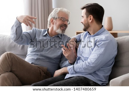 Smiling senior father sit on couch talk chat with millennial son spend time at home together, young man relax with elderly dad speak share thoughts have fun resting together on sofa in living room #1407480659