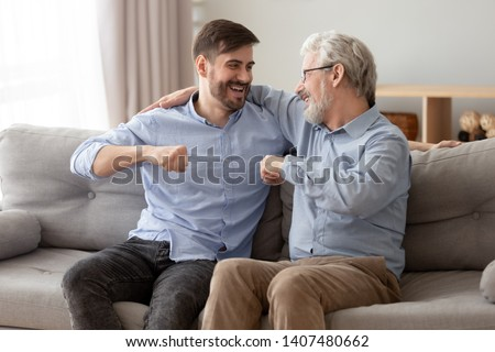 Excited millennial man sit on couch spend time with elderly father talking enjoying leisure time at home, smiling grown son relax on sofa with senior dad give fists bump, spend family weekend together #1407480662