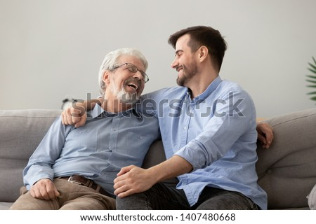 Smiling grown son sit on couch relax with senior dad talk sharing thoughts looking in eyes, happy millennial man rest on sofa speak with elderly father enjoy leisure family weekend at home #1407480668
