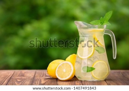 lemonade in glass jug on wooden table outdoors. Summer refreshing drink. Cold detox water with lemon #1407491843