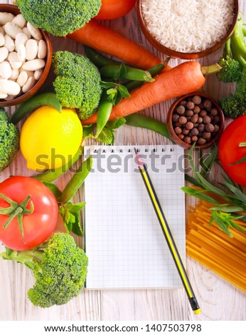Fresh food ingredients and notepad over wooden background #1407503798