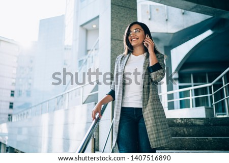 Turkish business woman in formal wear calling to colleague for discussing time of meeting on urban setting enjoying good roaming connection on smartphone device, concept of communication on phone #1407516890