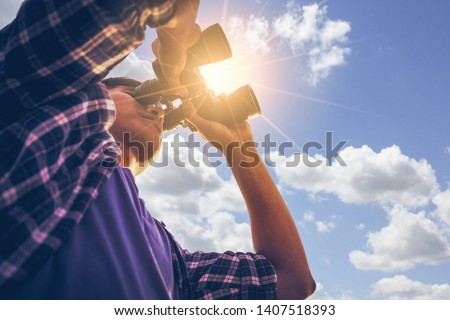 Close-up Of Asian man Hand Holding / looking / watching using Binoculars with copyspace, Technology Binoculars background concept Royalty-Free Stock Photo #1407518393