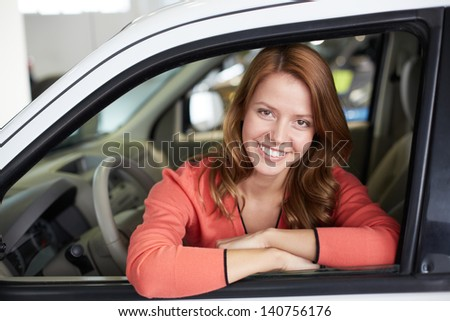 Photo of cute woman sitting in a new car and looking at camera #140756176