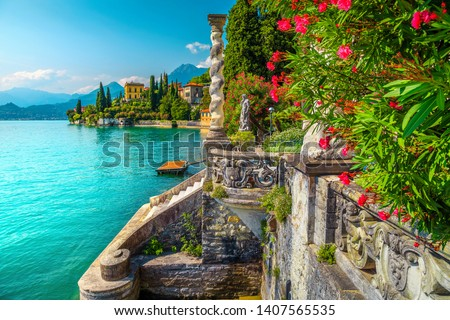 Picturesque landscape with lake and mediterranean buildings. Fresh oleander flowers and beautiful ornamental garden with villa Monastero, lake Como, Varenna, Lombardy region, Italy, Europe #1407565535