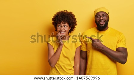 Studio shot of happy young woman and man look happily aside, point at blank space, notices awesome product, stand against yellow studio background. People, advertisement and ethnicity concept #1407569996