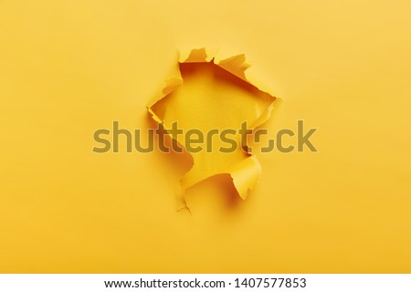 Small paper hole with torn sides over yellow background for your text, print or promotional content. Through paper. Ripped hole. No people. Accurate shot. Advertising and breakthrough concept #1407577853