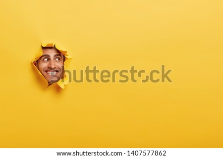 Glad Caucasian man with toothy smile, has bristle, looks positively aside, shows face in paper hole, isolated over yellow background with blank space. Positive emotions. Man peeks through ripped paper #1407577862