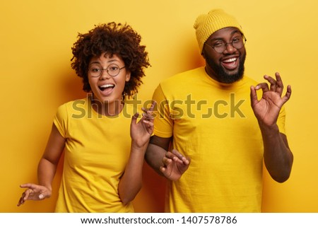 Photo of happy African couple dance together against yellow background, move body actively, show okay gesture, wear casual yellow t shirt, have fun during party. Monochrome. Feeling rhytm of music #1407578786