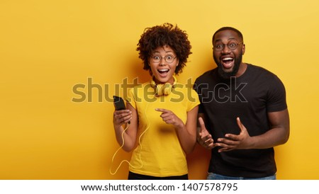 Overemotive dark skinned female holds cell phone, points at screen, listens music in headphones, optimistic man gestures from happiness, isolated over yellow background with empty space aside #1407578795