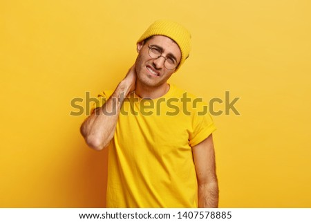 Overworked dissatisfied young European man keeps hand on neck, feels spasm in neck, tilts head, wears yellow hat and t shirt, poses over yellow background. People, tiredness and problem concept #1407578885