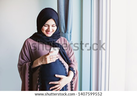 Young pregnant arab woman in hijab using her mobile phone to send message