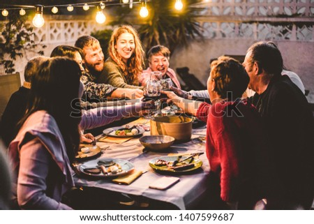 Happy family cheering with red wine at barbecue dinner outdoor - Different age of people having fun at weekend meal - Food, taste and summer concept - Focus on hands toasting #1407599687