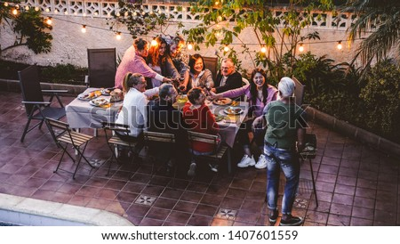 Happy family eating and cheering with red wine at barbecue party dinner - Different age of people having fun at bbq meal sitting in villa backyard - Summer lifestyle and food concept - Focus on faces #1407601559