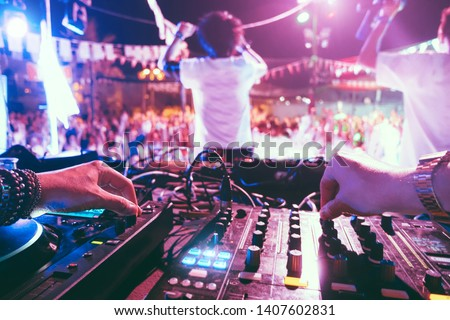 Dj mixing outdoor at beach party festival outdoor with crowd of people in background - Soft focus on left hand - Fun, summer, youth, nightlife, music, nightclubs and entertainment concept #1407602831