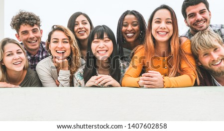 Happy millennial friends from diverse cultures and races having fun posing in front of smartphone camera - Youth and friendship concept - Young multiracial people smiling - Main focus on center faces #1407602858