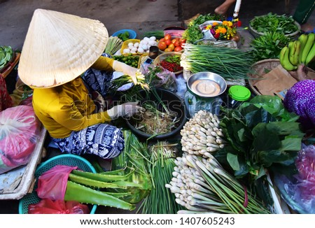 Vietnamese vendor sell vegetables in the  morning at local market in Vietnam Royalty-Free Stock Photo #1407605243