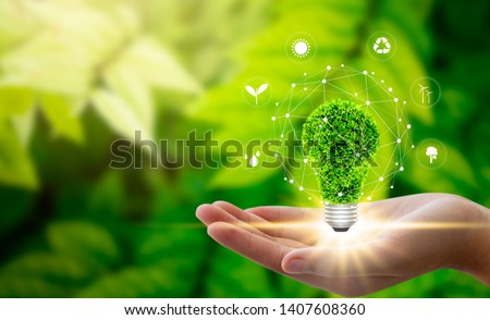 Hand holding light bulb against nature on green leaf with icons energy sources for renewable, sustainable development. Technology ,Environment ,Ecology concept. #1407608360