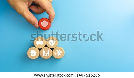 Insurance concept. Wooden blocks with insurance icons. family, life, car, travel, health and house insurance icons. blue background with copy space #1407616286