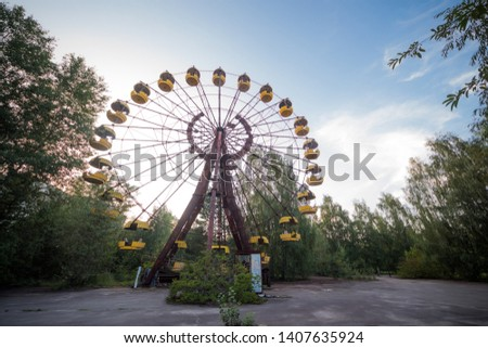 Ferris wheel on the main square of Pripyat. Abandoned attraction in a radioactive city. The street is overgrown with trees and bushes. #1407635924